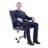 Giovane uomo di affari che si siede sulla sedia dell'ufficio isolata su bianco immagini stock libere da diritti