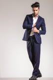 Giovane uomo di affari che sta e che tira il suo cappotto fotografia stock
