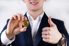 Giovane uomo di affari che tiene una moneta del bitcoin impiegatizio Simbolo di Cryptocurrency di bitcoin Soldi e fondo di invest Fotografia Stock