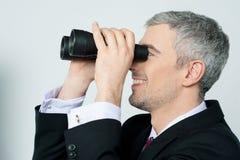 Giovane uomo di affari con binoculare Immagine Stock