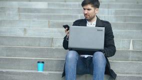 Giovane uomo di affari con il computer portatile che ha sforzo dopo la telefonata e che si siede sulle scale in via Uomo d'affari archivi video