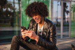 Giovane uomo di colore alla moda che utilizza Smart Phone nella città soleggiata fotografia stock