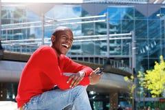 Giovane uomo di colore che ride nella città con il telefono cellulare Fotografia Stock Libera da Diritti