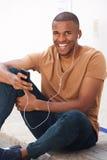 Giovane uomo di colore che si siede sulla terra e che ascolta la musica sullo Smart Phone Fotografia Stock Libera da Diritti