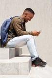 Giovane uomo di colore con la borsa che si siede sui punti che esaminano telefono cellulare Fotografia Stock