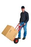 Giovane uomo di consegna isolato con il suo camion di mano Fotografia Stock