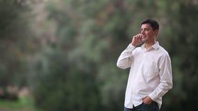 Giovane uomo di conversazione sul telefono nella natura stock footage