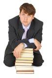Giovane uomo di erudizione con la pila di libri Immagini Stock