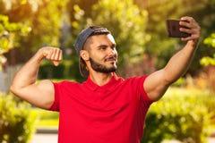 Giovane uomo di forma fisica che fa selfie nel parco di estate Immagine Stock
