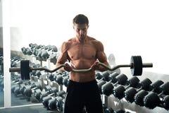Giovane uomo di forma fisica con l'ente muscolare che si esercita con la barra del ricciolo del ez Immagine Stock