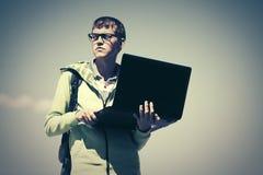 Giovane uomo di modo con il computer portatile sulla via della città Fotografia Stock