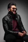 Giovane uomo di modo con la barba lunga che ride mentre distogliendo lo sguardo Fotografia Stock Libera da Diritti
