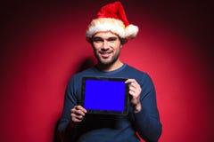 Giovane uomo di Santa che tiene un computer del cuscinetto della compressa dello schermo blu Immagini Stock Libere da Diritti