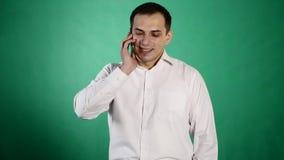 Giovane uomo di smiley che parla sul suo mobile Isolato su priorità bassa verde Conversazione del giovane al telefono cellulare stock footage