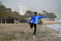 Giovane uomo di sport che allunga allenamento prima dell'correre sulla spiaggia davanti al primo mattino del mare Immagine Stock