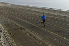 Giovane uomo di sport che corre da solo sulla spiaggia del deserto lungo l'allenamento di addestramento della riva di mare Fotografia Stock