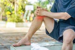 Giovane uomo di sport con le forti gambe atletiche che tengono ginocchio immagini stock libere da diritti