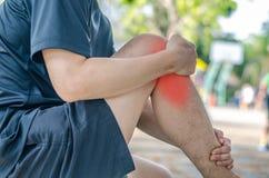 Giovane uomo di sport con le forti gambe atletiche che tengono ginocchio Fotografia Stock