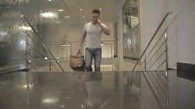 Giovane uomo di sport sulle scale nell'hotel e parlare sul telefono stock footage
