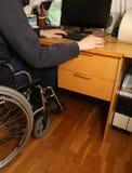 Giovane uomo disabile in una sedia a rotelle facendo uso del computer sul DES Fotografia Stock Libera da Diritti