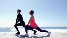 Giovane uomo e donna atletici che allungano sulla spiaggia Onde del mare sulla terra posteriore Movimento lento archivi video