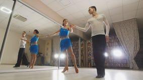 Giovane uomo e donna attraenti che ballano ballo dell'America latina in costumi nello studio, movimento lento, fine su, nell'azio fotografia stock