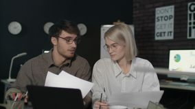 Giovane uomo e donna di affari che lavorano insieme computer portatile anteriore in ufficio scuro archivi video