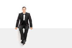 Giovane uomo elegante che si siede su un pannello in bianco Immagini Stock Libere da Diritti