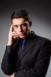 Giovane uomo elegante contro gray Immagini Stock