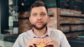 Giovane uomo esile barbuto affamato che gode mordendo piacere ritenente dell'hamburger saporito che esamina macchina fotografica video d archivio