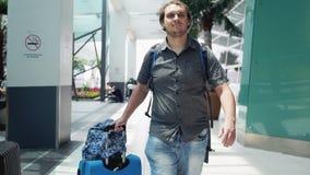 Giovane uomo felice barbuto con lo zaino che tira valigia in terminale di aeroporto moderno Allontanarsi bello di viaggio del tip immagine stock