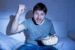 Giovane uomo felice a casa che guarda la partita di sport sulla TV che incoraggia il suo gruppo che gesturing il pugno di vittori Fotografie Stock