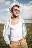 Giovane uomo felice che posa in un campo con i fiori Immagini Stock Libere da Diritti