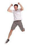 Giovane uomo felice che salta su una priorità bassa bianca Fotografia Stock Libera da Diritti