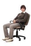 Giovane uomo felice che si siede su una presidenza di rotella. Immagini Stock
