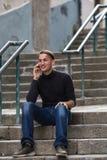 Giovane uomo felice che si siede sulle scale all'aperto che parlano sul telefono Fotografia Stock Libera da Diritti