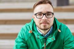 Giovane uomo felice dei pantaloni a vita bassa che si siede sulle scale in città fotografia stock