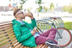 Giovane uomo felice dei pantaloni a vita bassa con caffè ed il panino immagini stock libere da diritti