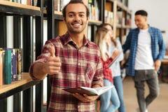 Giovane uomo felice dello studente che sta nella biblioteca che mostra i pollici su Immagine Stock