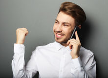 Giovane uomo felice di affari in camicia che gesturing e che sorride mentre t Immagine Stock