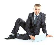 Giovane uomo felice di affari che lavora ad un computer portatile Immagine Stock
