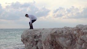 Giovane uomo felice sedersi sull'alta collina di roccia e di godere della vista stupefacente della spiaggia e di bello tempo cypr archivi video