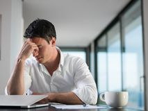 Giovane uomo frustrato di affari che lavora al computer portatile a casa Fotografie Stock