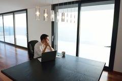 Giovane uomo frustrato di affari che lavora al computer portatile a casa Fotografia Stock Libera da Diritti