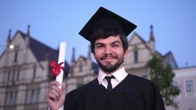 Giovane uomo graduato felice caucasico che posa alla macchina fotografica e che mostra il suo diploma davanti all'università stock footage