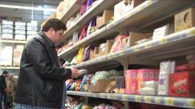 Giovane uomo grasso che seleziona caramella dolce, dessert in supermercato nell'alta qualità stock footage