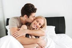 Giovane uomo grazioso che bacia e che abbraccia la sua moglie felice immagini stock