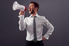 Uomo gridante che per mezzo del megafono Fotografia Stock Libera da Diritti