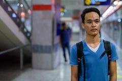 Giovane uomo indiano bello alla stazione ferroviaria del sottopassaggio a Bangkok Immagine Stock