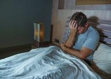 Giovane uomo insonne triste e depresso che si trova sul ritenere a casa preoccupato e premuroso del letto della camera da letto d fotografia stock libera da diritti